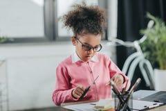 Bambina in occhiali che tengono le forbici e che tagliano carta alla tavola dell'ufficio Fotografie Stock Libere da Diritti