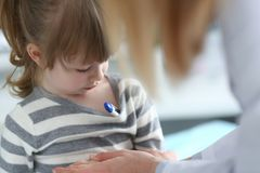 Bambina pensierosa sveglia con il termometro sotto la sua ascella fotografia stock libera da diritti