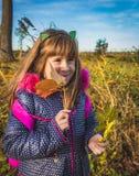 Bambina piacevole con le foglie di autunno alla luce del tramonto fotografia stock libera da diritti