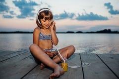 Bambina positiva con le cuffie che ascolta la musica fotografie stock