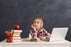Bambina premurosa che fa compito sul computer portatile Fotografia Stock