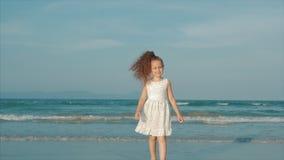 Bambina riccia in vestito bianco che cammina sulla spiaggia al tramonto Movimento lento Infanzia, libertà e viaggio felici stock footage