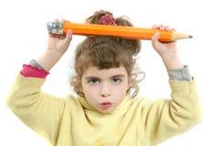 Bambina seria con la grande matita a disposizione Immagini Stock Libere da Diritti