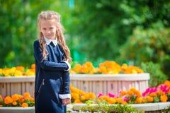 Bambina smilling sveglia che posa davanti alla sua scuola sopra in primo luogo di settembre Bambino adorabile che ritiene molto e Fotografia Stock Libera da Diritti