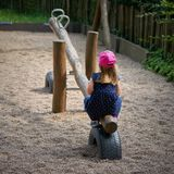 Bambina sola su un campo da giuoco fotografia stock libera da diritti