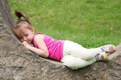 Bambina sonnolenta che riposa su Stonewall nel parco Fotografia Stock Libera da Diritti