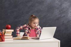 Bambina sorpresa che fa compito sul computer portatile Immagine Stock Libera da Diritti