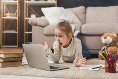 Bambina sorpresa che fa compito sul computer portatile, trovantesi sul pavimento Fotografia Stock
