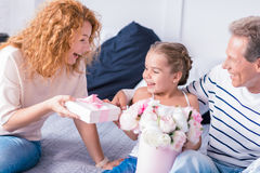 Bambina sorpresa che riceve un presente dai suoi nonni Immagini Stock
