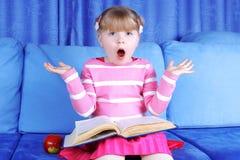 Bambina sorpresa con la mela ed il libro Fotografia Stock