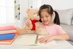 Bambina sorridente che fa compito con il suo orsacchiotto Fotografie Stock Libere da Diritti