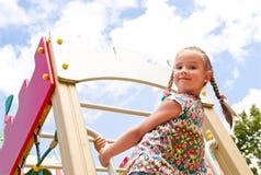 Bambina sorridente che gioca sull'attrezzatura del campo da giuoco Immagine Stock