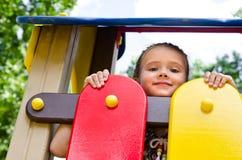 Bambina sorridente che gioca sull'attrezzatura del campo da giuoco Fotografia Stock