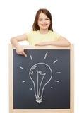 Bambina sorridente che indica dito la lavagna Fotografie Stock Libere da Diritti