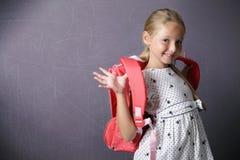 Bambina sorridente che indossa uno zaino per la scuola Fotografie Stock Libere da Diritti