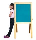 Bambina sorridente che si leva in piedi al lato di una lavagna Immagine Stock Libera da Diritti