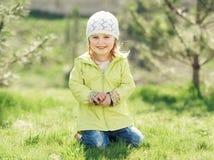 Bambina sorridente che si siede su un prato inglese nel parco Fotografie Stock Libere da Diritti