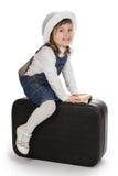 Bambina sorridente che si siede su una valigia Immagine Stock