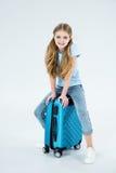 Bambina sorridente che si siede sulla borsa di viaggio immagini stock
