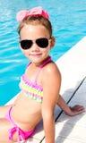 Bambina sorridente che si siede vicino alla piscina Immagine Stock