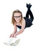 Bambina sorridente che si trova con un libro aperto Fotografia Stock