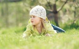 Bambina sorridente che si trova su un prato inglese nel parco Immagine Stock
