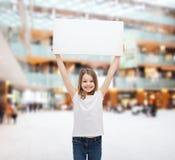 Bambina sorridente che tiene bordo bianco in bianco Immagine Stock