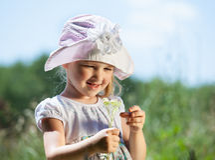 Bambina sorridente che tiene i fiori selvaggi Fotografia Stock
