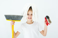 Bambina sorridente che tiene i vari rifornimenti di pulizia su bianco fotografia stock