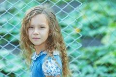 Bambina sorridente con capelli ricci vicino al recinto della griglia immagine stock