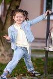Bambina sorridente con gli occhi scuri, taglio di capelli sotto forma di treccia Immagini Stock