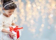 Bambina sorridente con il contenitore di regalo sopra le luci fotografia stock libera da diritti