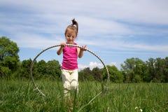 Bambina sorridente con il hula-hoop che gode di bello giorno di primavera nel parco Fotografia Stock Libera da Diritti