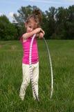 Bambina sorridente con il hula-hoop che gode di bello giorno di primavera nel parco Immagini Stock Libere da Diritti
