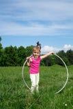 Bambina sorridente con il hula-hoop che gode di bello giorno di primavera nel parco Fotografie Stock