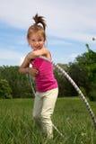 Bambina sorridente con il hula-hoop che gode di bello giorno di primavera nel parco Immagine Stock