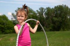 Bambina sorridente con il hula-hoop che gode di bello giorno di primavera nel parco Immagine Stock Libera da Diritti