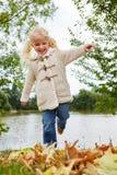 Bambina sorridente con le foglie di autunno fotografie stock