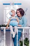 Bambina sorridente con sua sorella più anziana che sta accanto ad un Chr fotografia stock libera da diritti