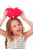 Bambina sorridente con un cuore rosso immagini stock