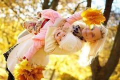 Bambina sorridente della tenuta della donna con le foglie di autunno Immagine Stock Libera da Diritti