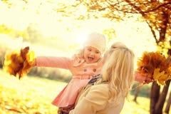 Bambina sorridente della tenuta della donna con le foglie di autunno Immagini Stock