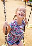 Bambina sorridente divertendosi su un'oscillazione nel parco Fotografie Stock