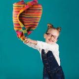 Bambina sorridente divertente con il grande zaino che salta e che ha f Immagini Stock Libere da Diritti