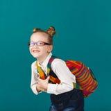 Bambina sorridente divertente con il grande zaino che salta e che ha f Fotografia Stock Libera da Diritti