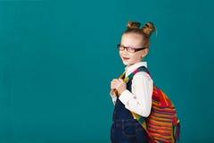 Bambina sorridente divertente con il grande zaino che salta e che ha f Fotografie Stock Libere da Diritti