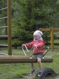 Bambina sorridente sull'oscillazione del campo da giuoco Fotografia Stock