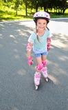 Bambina sorridente sveglia nei pattini di rullo rosa fotografia stock