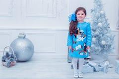 Bambina sorridente in un vestito grigio sopra Immagini Stock