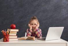 Bambina stanca che fa compito sul computer portatile Immagine Stock Libera da Diritti